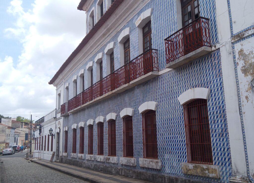 Fabrica Santa Amélia. O prédio possui três andares e é revestido com azulejos em azul e branco.